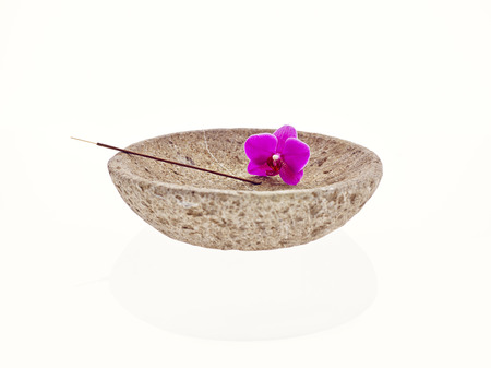 Bowl with blossom and joss stick photo
