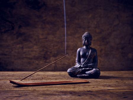 Buddha lit on wood with joss stick Stockfoto