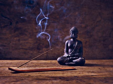 joss: Buddha lit on wood with joss stick Stock Photo