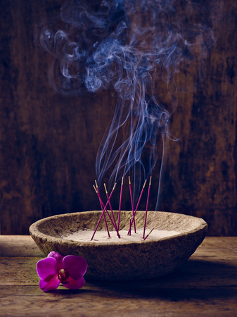 Bowl with joss sticks lit on wood and bloom