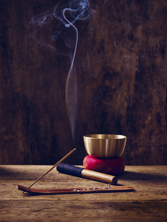 Lit singing bowl on wood with joss stick