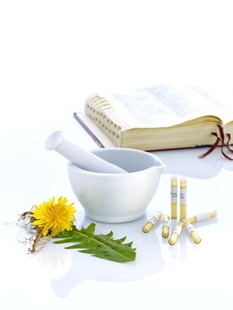 white mortar with book glass tubes and dandelion Stock Photo