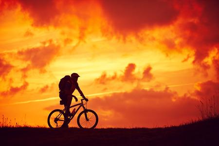 Man and mountain biking pleasure red clouds
