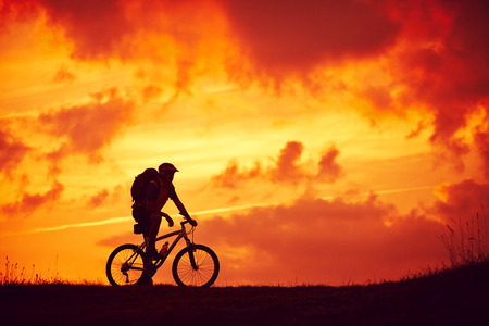 Man and mountain biking pleasure red clouds