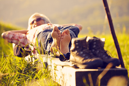 plantar: Man with walking map in meadow lying Stock Photo