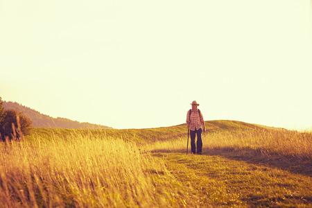hombre con sombrero: Hombre caminando en el sol de la tarde en el camino