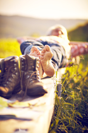 walking boots: Hiker lying with walking boots on bench and meadow