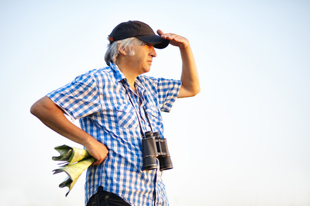 recognize: Hiker with a plaid shirt, binoculars and hiking map