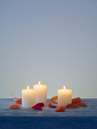 esoterismo: Luz de las velas y las hojas sobre la mesa de madera