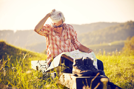 Man with walking map and shoes sitting in meadow
