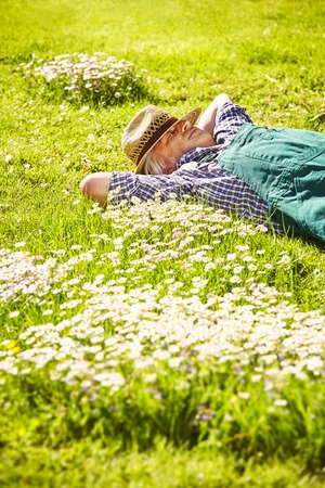 dormant: Gardener lies dormant with straw hat in meadow