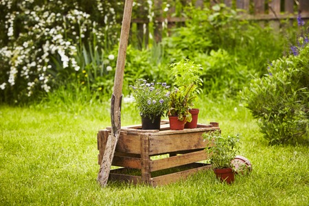 Wooden box with spade and straw hat in the garden