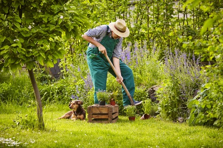 麦わら帽子の庭での作業を持つ男