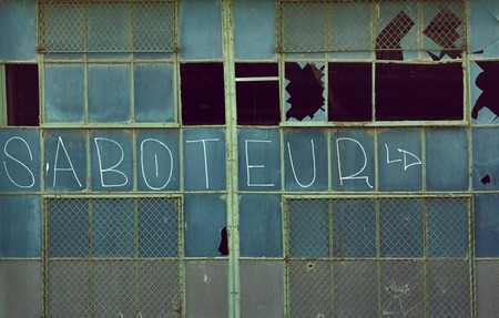 sabotage: Factory gate with windows and graffiti in Detroit Packard Plant USA