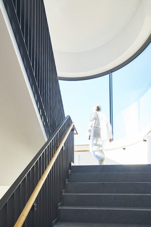 stairwell: Doctor from behind on stairs in stairwell with large windows with sun and blue sky