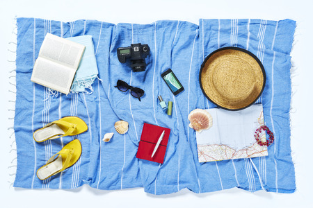 flatlay from above white beach with hat sandals towel sunglasses camera on blue towel