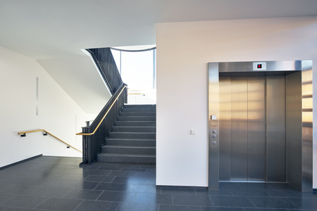 Stairs in stairwell with large windows and lift