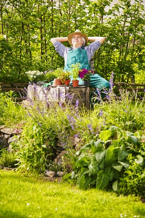 herbs boxes: Gardener with straw hat and plants, flowers and herbs in the garden relaxing Stock Photo