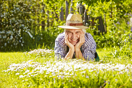 lean on hands: Gardener lying in a flower meadow of daisys in the sun wit a straw hat