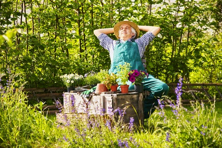 stretch out: Gardener relaxing with straw hat and plants, flowers and herbs in the garden Stock Photo