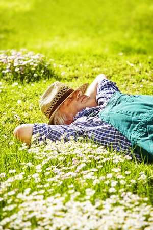 naptime: Gardener lies sleeping with straw hat in meadow of daisys