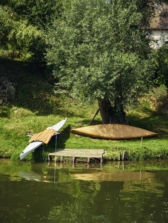 two kayaks lie on the bank of a canal with meadow in summer Stockfoto