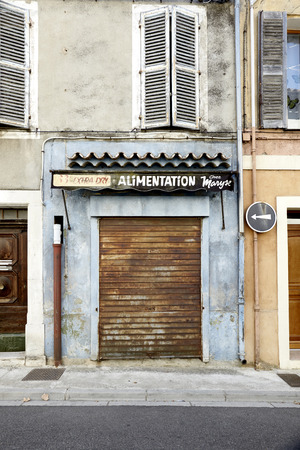 Business food alimentation old and closed with shutters made of metal on a house