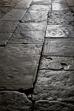 Stone old floor with grave plate with inscription in a church in the back light