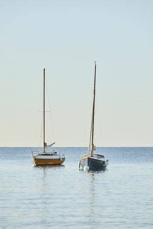 Two sailboats small at anchor with buoy on the sea