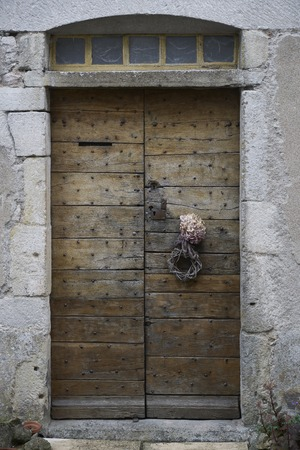 Wooden old and dark wood door and metal rivets with wooden wreath on a building