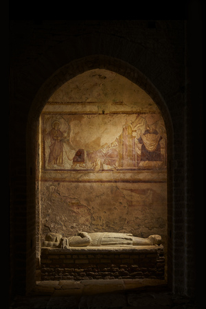 Sarcophagus in a church with fresco on the wall and bleached