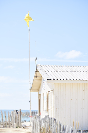 Hut on a beach with yellow flag and sea view with sky and clouds