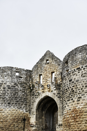 Entrance and loopholes with door at a castle with round arch made of stone