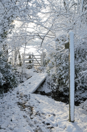 externals: Snow covered woodland footpath leading to timber kissing gate giving access to public footpath across farmland Essex England UK