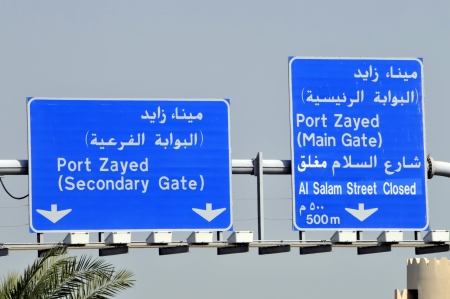 bilingual: Abu Dhabi blue bilingual motorway type sign on gantry above road