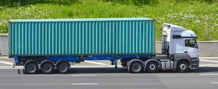 Shipping container on articulated trailer and lorry on UK motorway photo