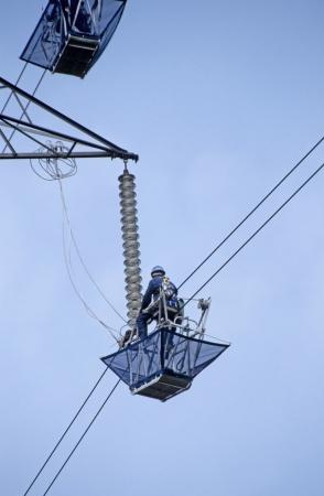 pylon: Maintenance workmen in cradles on overhead high voltage electricity power line and pylon England UK