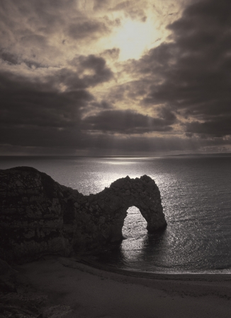 durdle: Sun breaking through storm clouds around Durdle Dor rock formation on the Dorset Jurassic Coast  also known as Durdle Door