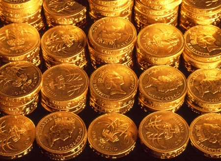 Stacked pound coins in organised regular rows under tungsten lighting to give a golden hue photo