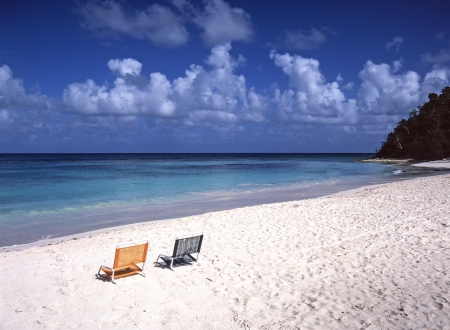 antigua: White sand Caribbean beach and empty chairs