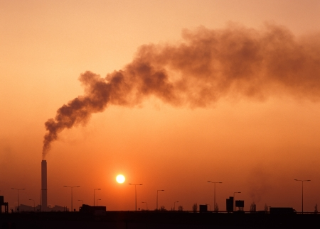 emissions: Power station chimney and smoke beyond motorway with full sun