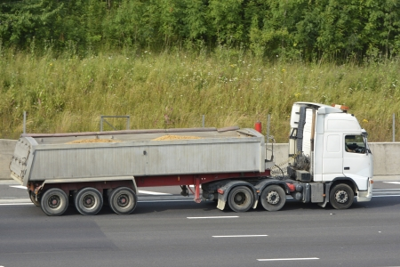 haulage: Lorry with articulated tipper trailer carrying sand travelling along motorway