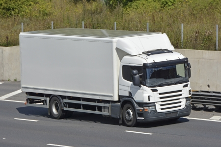 along: White unmarked rigid body lorry driving along motorway