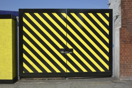 hoarding: Padlocked access gates in hoarding around plot of land awaiting redevelopment
