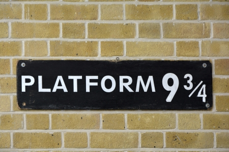 Sign on wall at Kings Cross station visited by fans of Harry Potter and  Platform nine and three quarters  photo