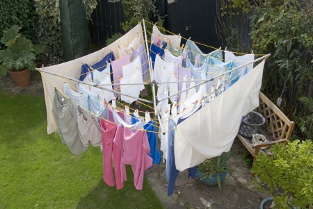 CLOTHES HANGING: Washing hanging out to dry on a rotary clothes line in a domestic garden Stock Photo