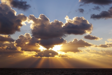 the setting sun: Suns rays bursting through clouds over sea