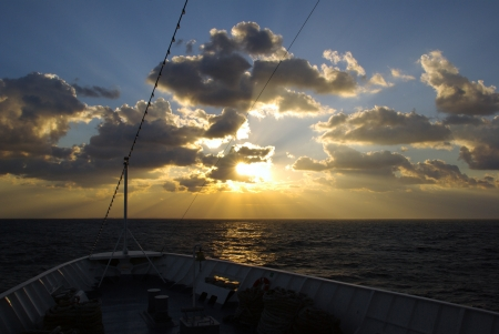 sunsets: Bow of cruise ship and view of suns rays bursting through clouds over sea