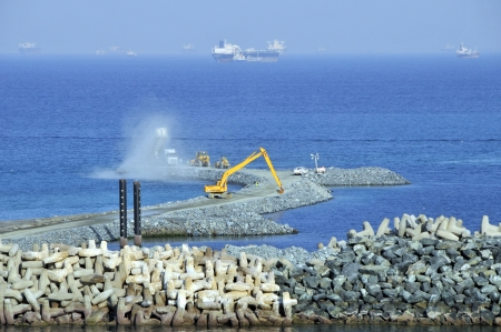 breakwaters: Extending port facilities beyond existing Dolos concrete blocks that form harbour wall on approach to Fujairah docks in United Arab Emirates