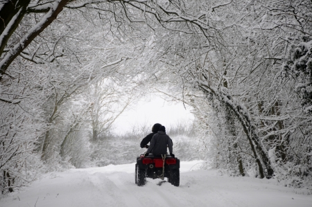 inclement: Driving quad bike through a snow covered winter wonderland tunnel along country lane